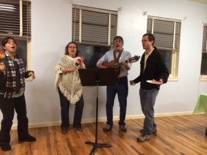 Viviana Susa Parra, Gloria Piper, Denys Vigil, & Rick Clifford lead DJPC in singing at the 2014 Holiday Party